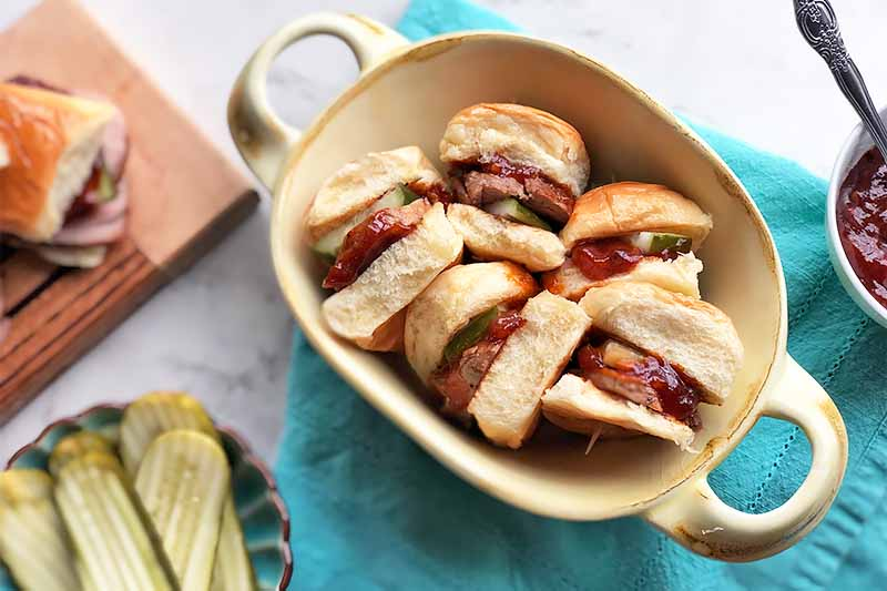 Horizontal image of a platter with mini sandwiches on a blue towel next to sliced pickles and red sauce in a bowl.
