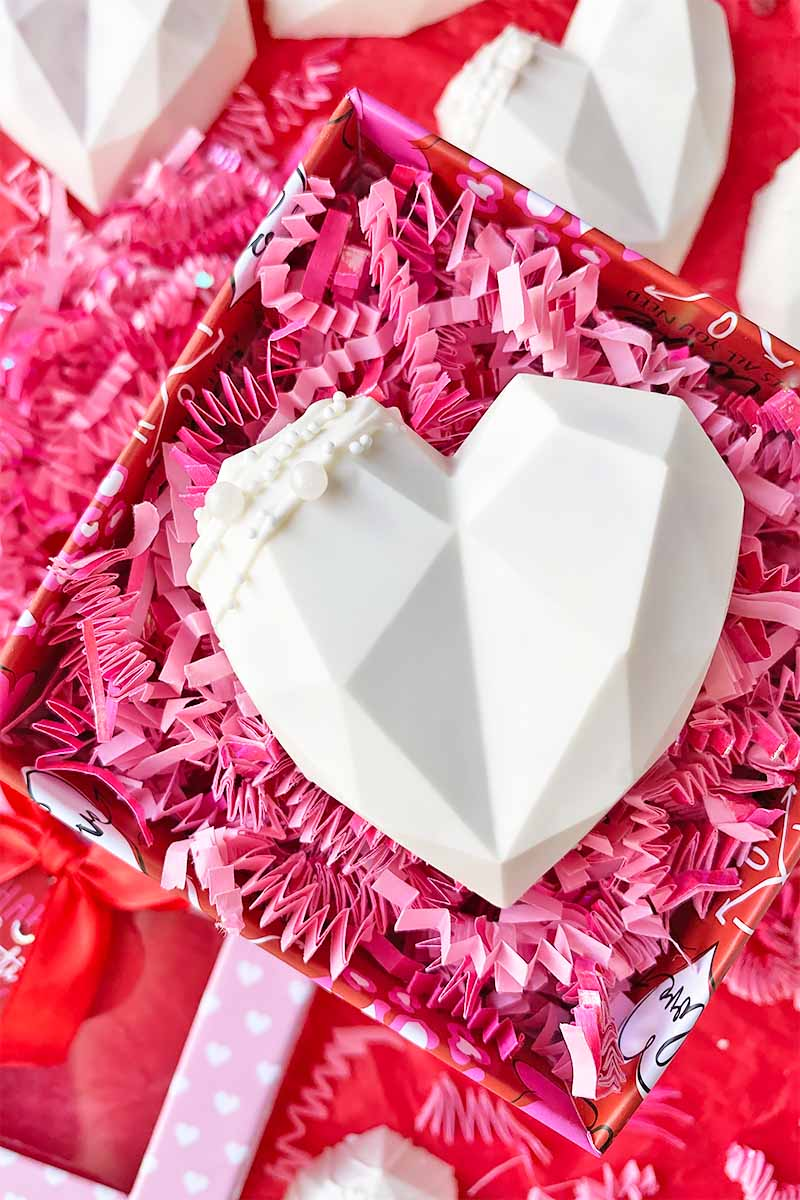 Vertical image of a white heart dessert in a box with pink confetti.