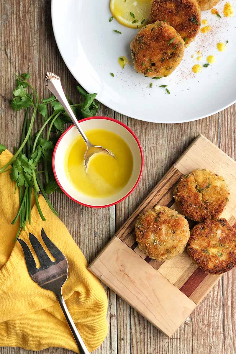 Vertical top-down image of crab cakes on a white plate and a wooden cutting board next to a bowl of yellow sauce and a serving fork on a yellow towel next to fresh herbs.