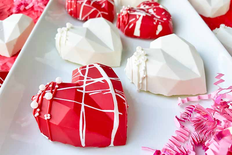 Horizontal image of decorated red and white chocolate shells on a white plate next to pink confetti.