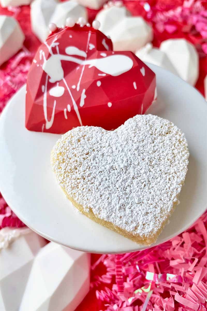 Vertical image of a heart-shaped cake and edible covering in a splatter paint design on a small white stand.