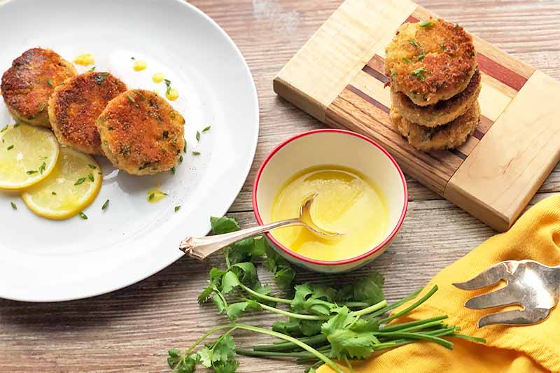 Horizontal image of a stacked and shingled browned seafood cakes on a white plate and on a wooden cutting board next to a bowl of yellow dip, herbs, and silverware on a yellow towel.