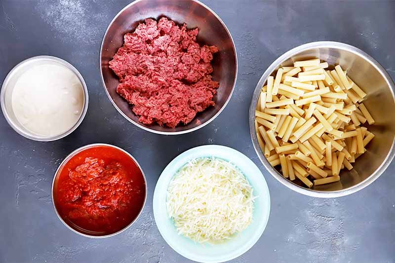 Horizontal image of bowl of raw ground meat, pasta, cheese, tomato puree, and a white liquid.