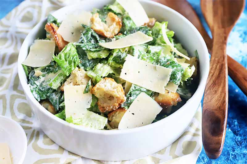 Horizontal image of a large white bowl filled with a green salad topped with shaved cheese and toasted bread cubes, next to wooden spoons on a blue surface.