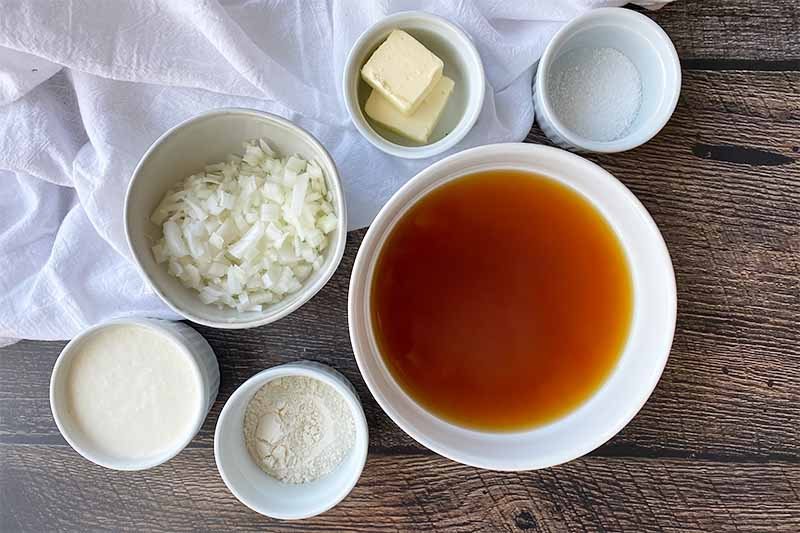 Horizontal image of white bowls filled with stock, chopped onions, seasonings, and butter.