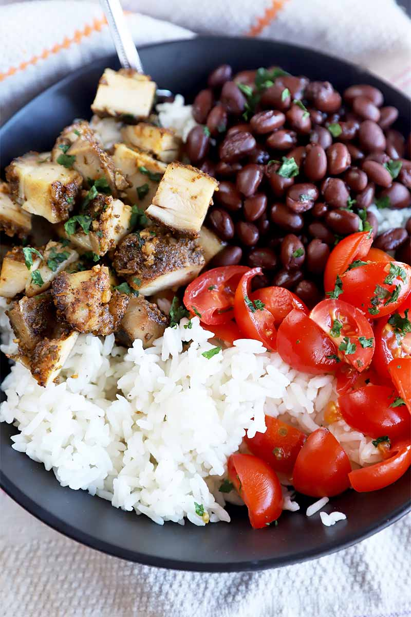 Vertical image of a burrito bowl with beans, chicken, and tomatoes in a black dish.