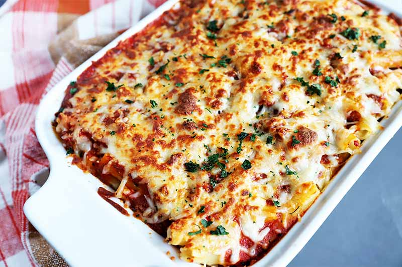 Horizontal image of a whole baked ziti in a white baking dish.