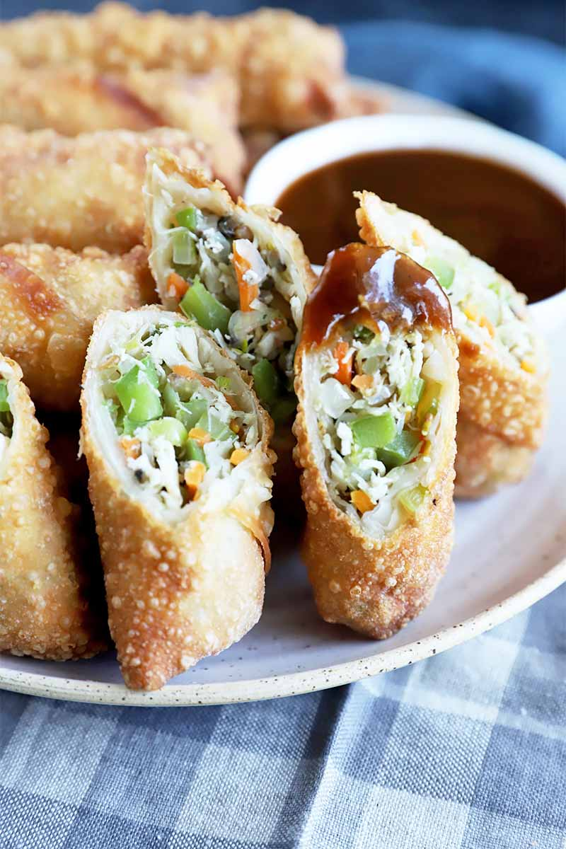 Vertical image of halved egg rolls, with on dipped in a dark liquid, on a plate over a blue checkered napkin.