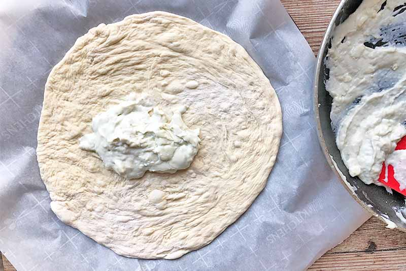 Horizontal image of an unbaked round of dough topped with a mound of thick white sauce on parchment paper.