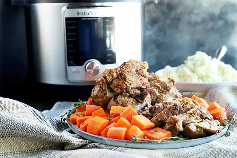 Horizontal image of a large plate full of chopped cooked carrots and sliced cooked meat on top of a tan towel in front of a kitchen appliance.