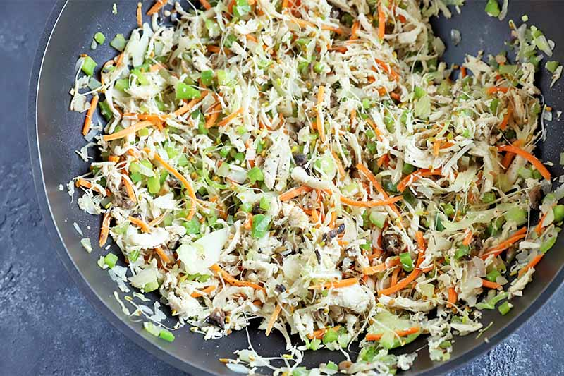 Horizontal image of a vegetable and shredded chicken mixture in a pan.