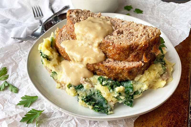 Horizontal image of two slices of a ground beef dish served with gravy over mashed kale potatoes on a white plate on a white towel.