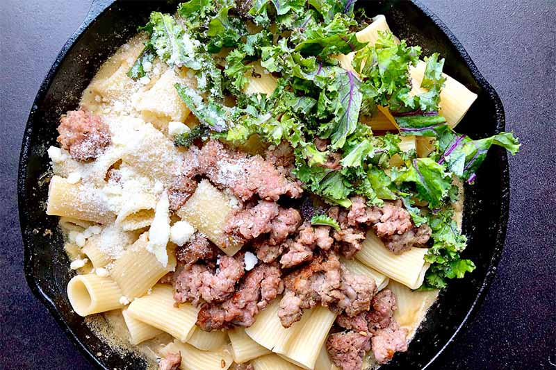 Horizontal image of cooking pasta, crumbled meat, chopped kale, and a tan sauce in a cast iron skillet.