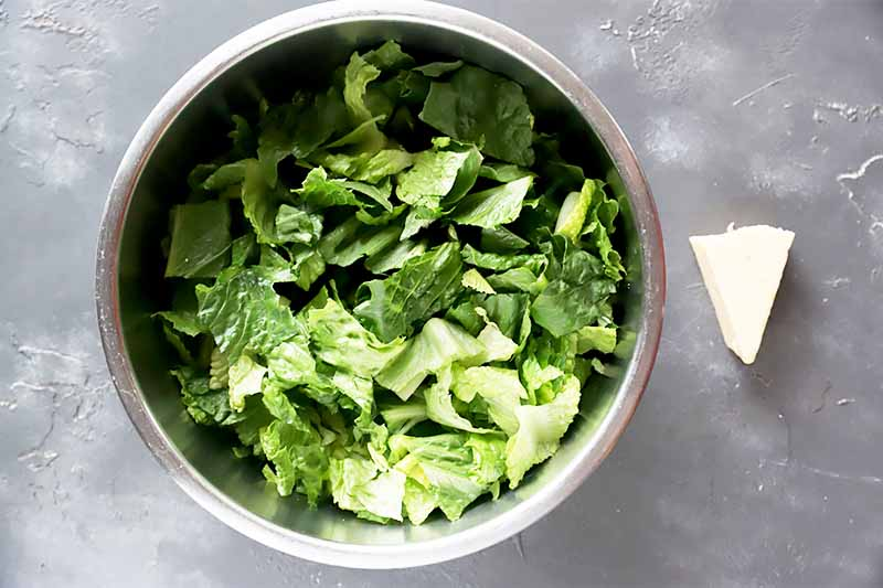 Horizontal image of a metal bowl full of shaved green lettuce next to a wedge of cheese.