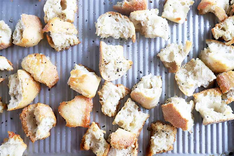 Horizontal image of toasted bread cubes on a metal baking sheet.