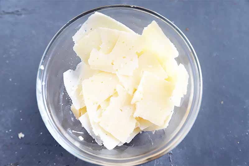 Horizontal image of a glass bowl with shaved cheese.