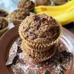 Horizontal image of a stack of muffins on a brown plate in front of more baked goods and bananas.