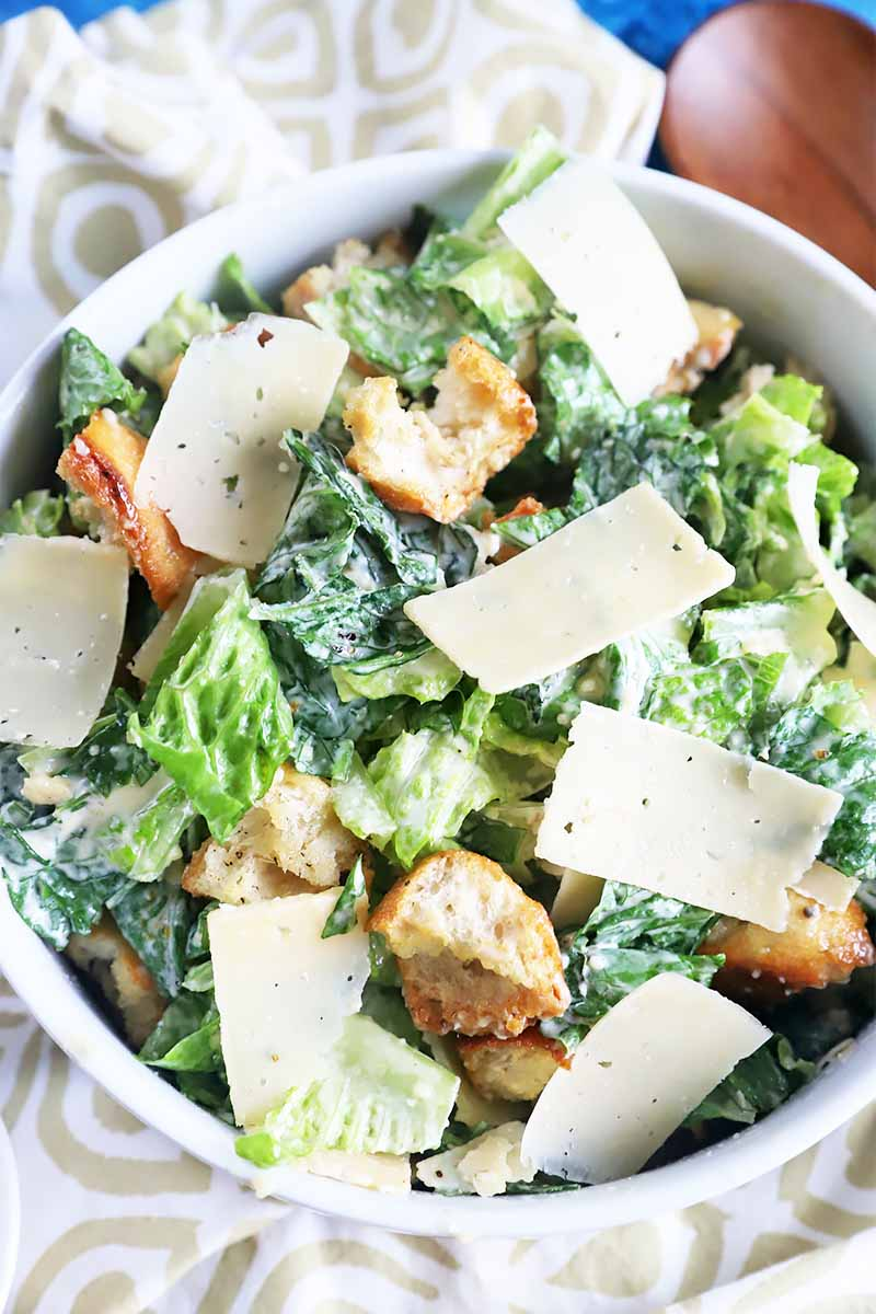 Vertical image of a large white bowl with Caesar salad.