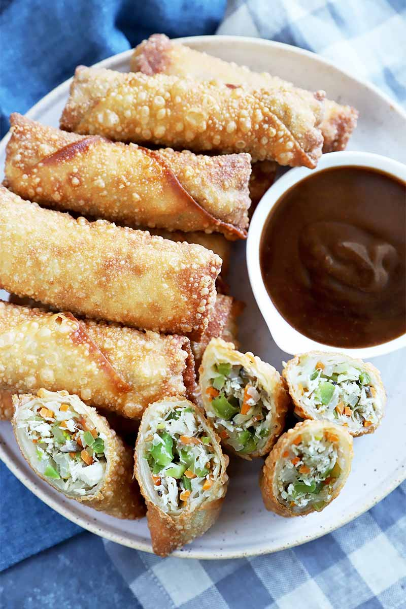 Vertical image of whole and sliced egg rolls on a platter with a dipping sauce on the side.