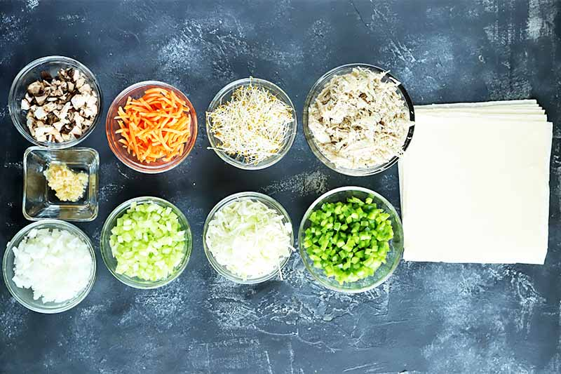 Horizontal image of assorted chopped vegetables in glass bowls next to a stack of square wonton wrappers.