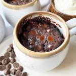Horizontal image of a chocolate dessert baked in cups next to a bowl of whipped cream.