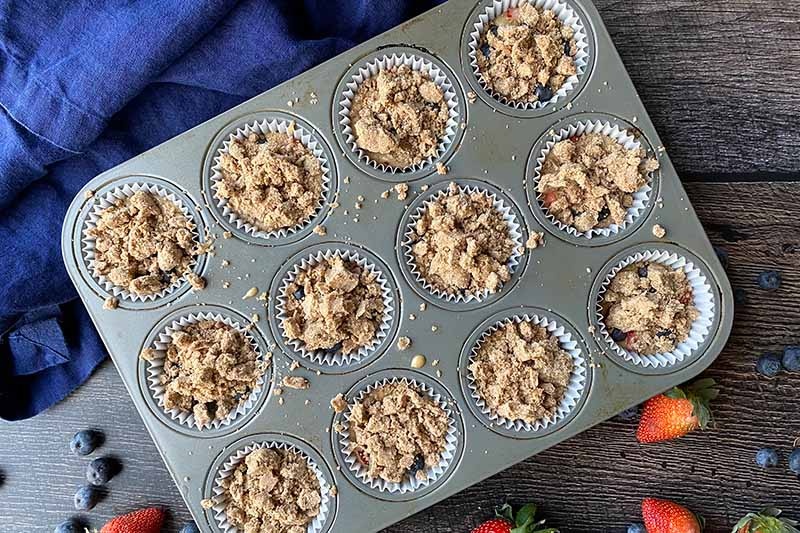 Horizontal image of cups of batter in a pan topped with streusel.
