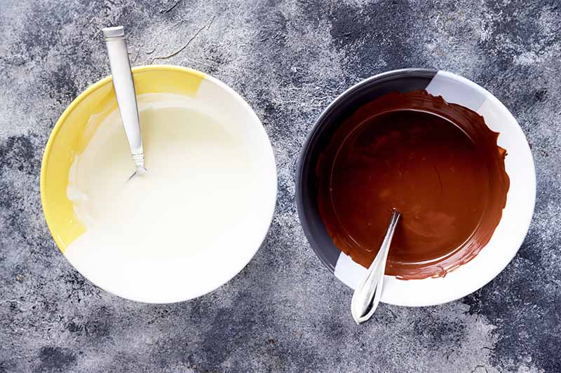 Horizontal image of melted white and dark chocolate in bowls with spoons.