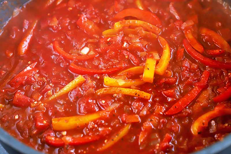 Horizontal image of a cooked sauce of stewed tomatoes and bell peppers.