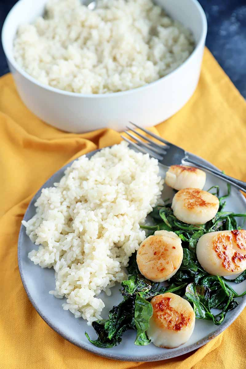 Vertical image of a white bowl and a plate of white rice, with scallops and greens on the plate on a yellow towel.