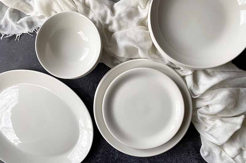 Horizontal top-down image of assorted sizes of white dishes on a dark surface on top of a white towel.
