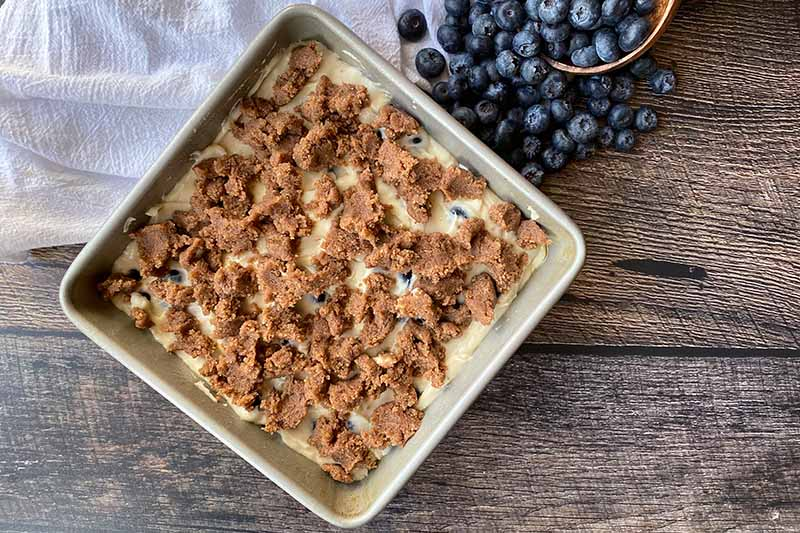Horizontal image of unbaked batter and streusel topping in a square pan.