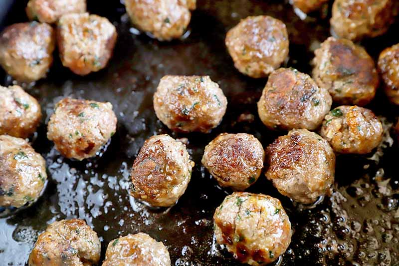 Horizontal image of cooking meatballs in a greased skillet.