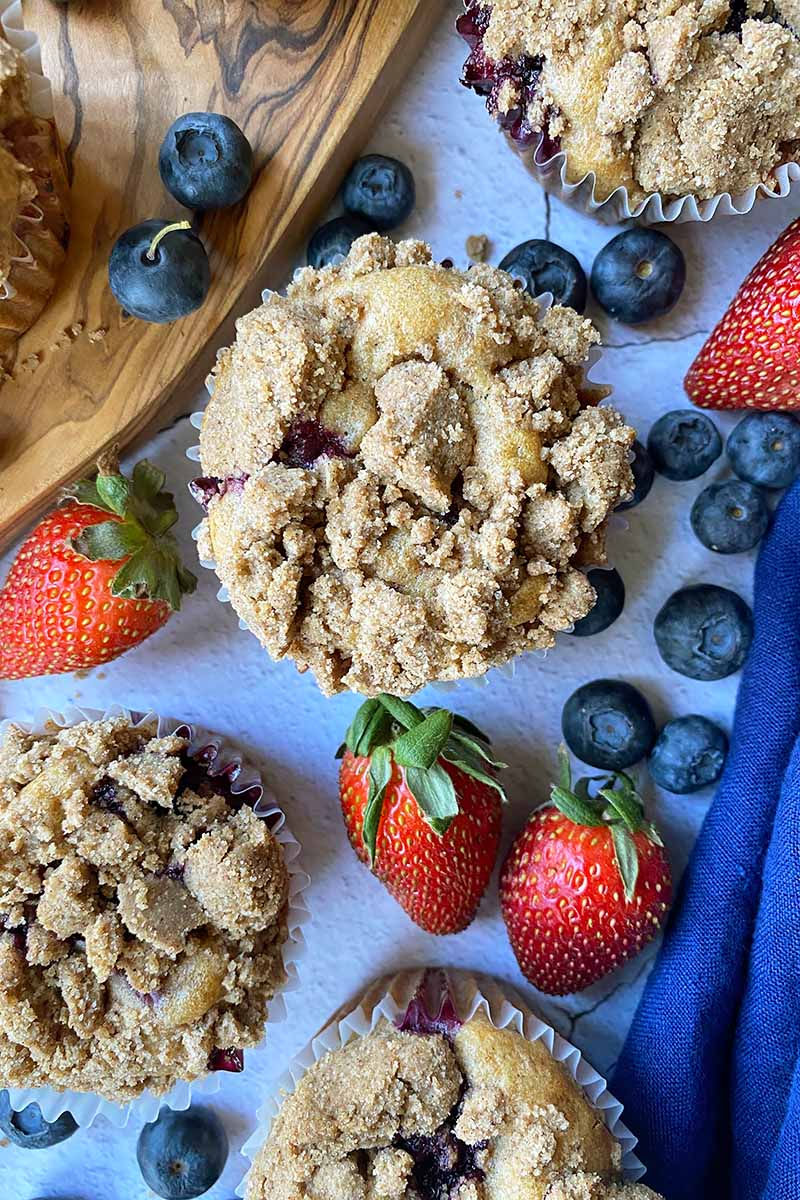 Vertical top-down image of circular baked goods topped with streusel on a surface scattered with fresh fruit.