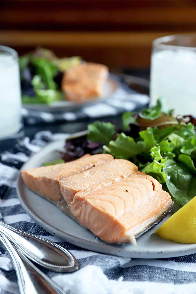 Vertical image of an unseasoned cooked piece of pink fish on a plate next to a lemon and salad greens, with silverware on the side of the plate.