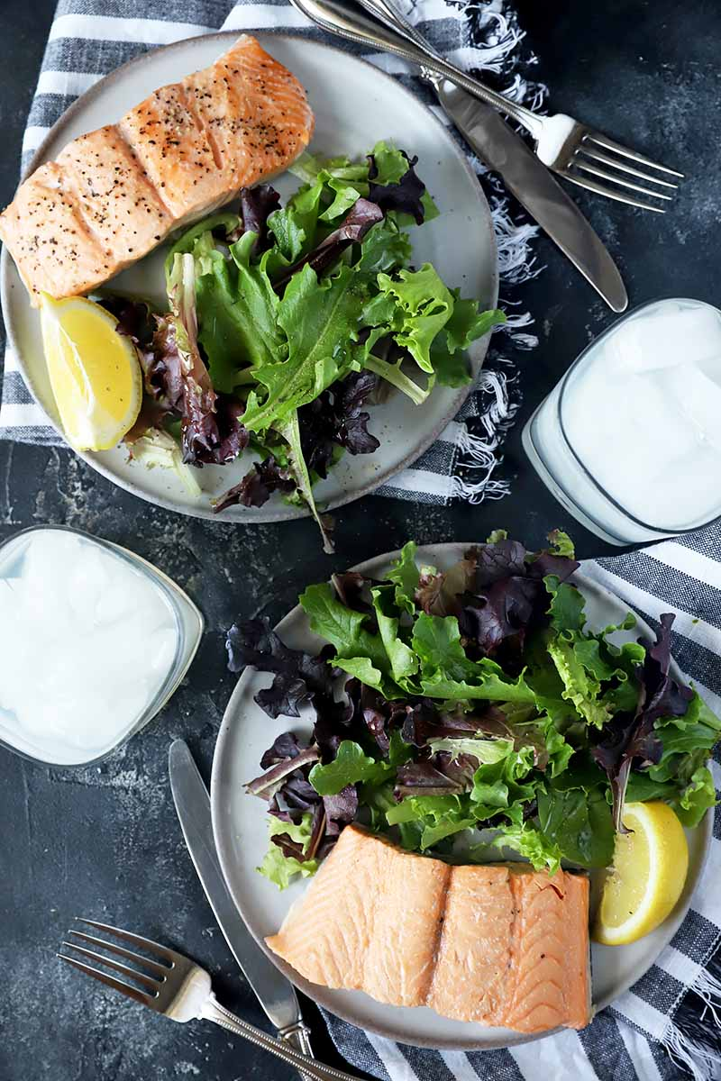 Vertical top-down image of two plates with cooked pink fish fillets, salad greens, and lemon wedges next to cocktails and silverware.