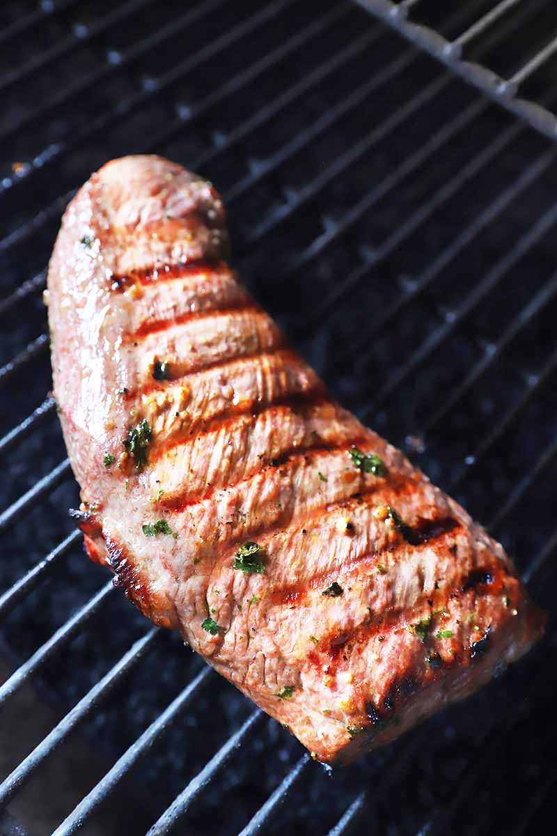 Vertical image of a large piece of meat with herbs cooking on a grill.