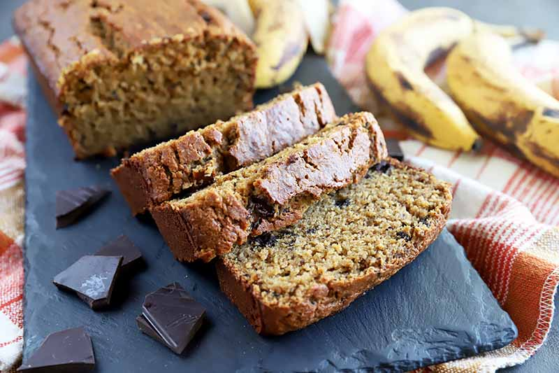 Horizontal image of slices of banana bread on a slate next to fruit and chocolate chunks.