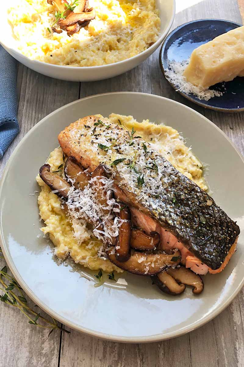 Vertical image of a gray plate with cooked cornmeal, mushrooms, and a seafood fillet