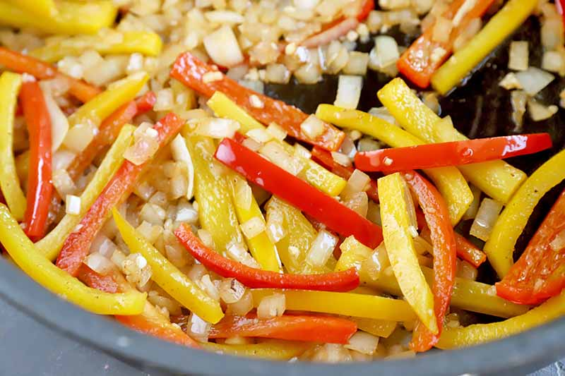 Horizontal image of cooking sliced yellow and red bell peppers with aromatics in a skillet.