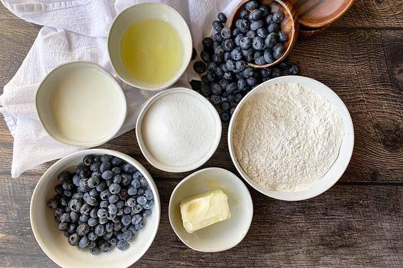 Horizontal image of various dry ingredients, wet ingredients, and fresh fruit in bowls.
