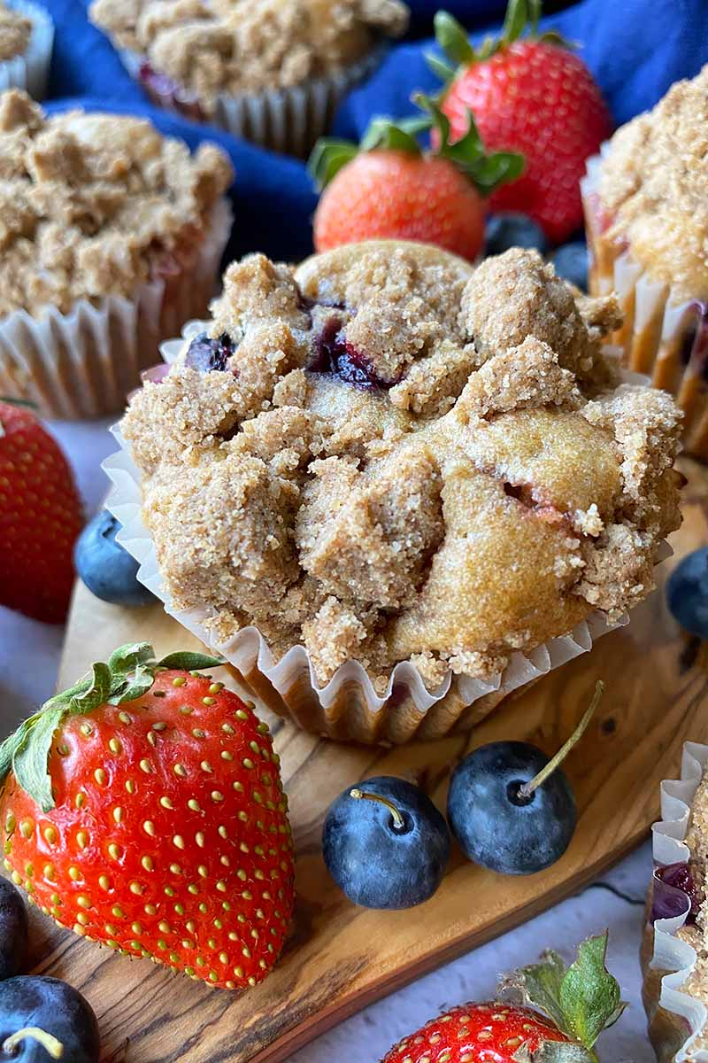 Vertical image of baked goods in paper liners topped with crumbles on a wooden board surrounded by fresh fruit.