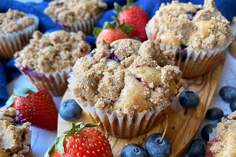Horizontal image of baked goods in paper liners topped with crumbles on a wooden board surrounded by fresh fruit.