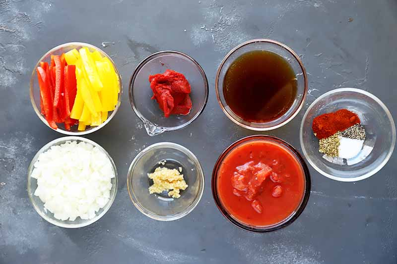 Horizontal image of prepped vegetables and seasonings in small glass bowls.