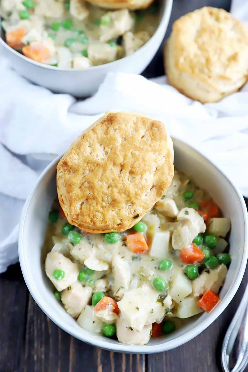 Vertical top-down image of white bowls filled with a thick and creamy savory mixture of peas, carrots, potatoes, and white meat with golden biscuits.