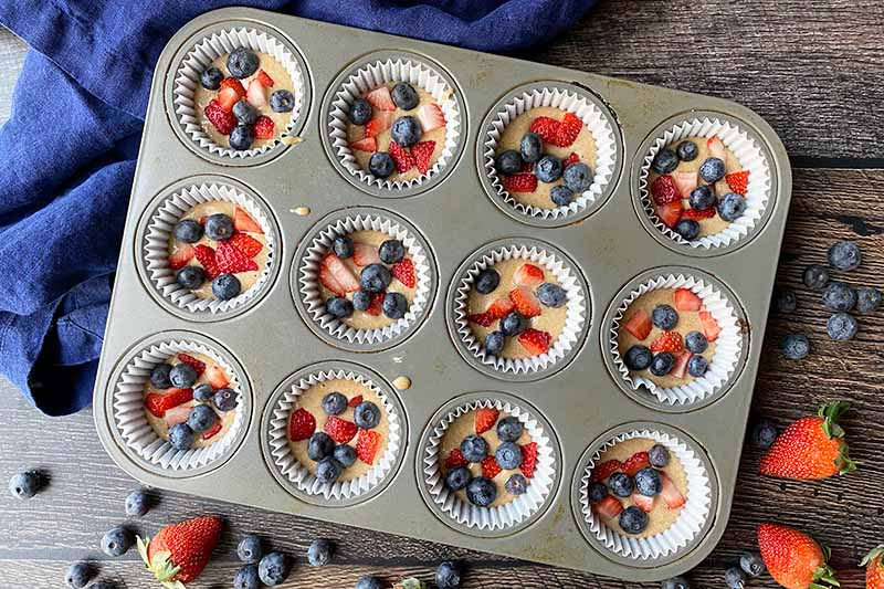 Horizontal image of batter topped with fresh pieces of fruit in cups in a pan.
