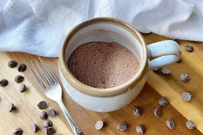 Horizontal image of dry ingredients in a mug on a wooden board surrounded by candies and a fork.
