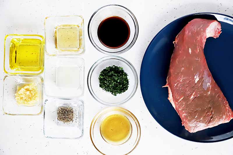 Horizontal image of various wet and dry ingredients in glass bowls and a large cut of raw meat on a blue plate.