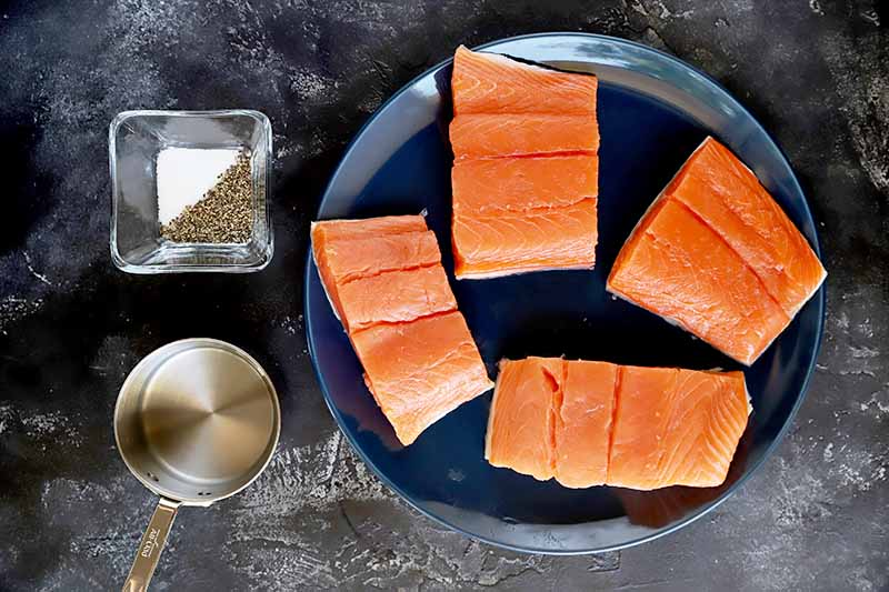 Horizontal image of raw fish fillets on a plate next to small glass bowls of liquid and salt and pepper.