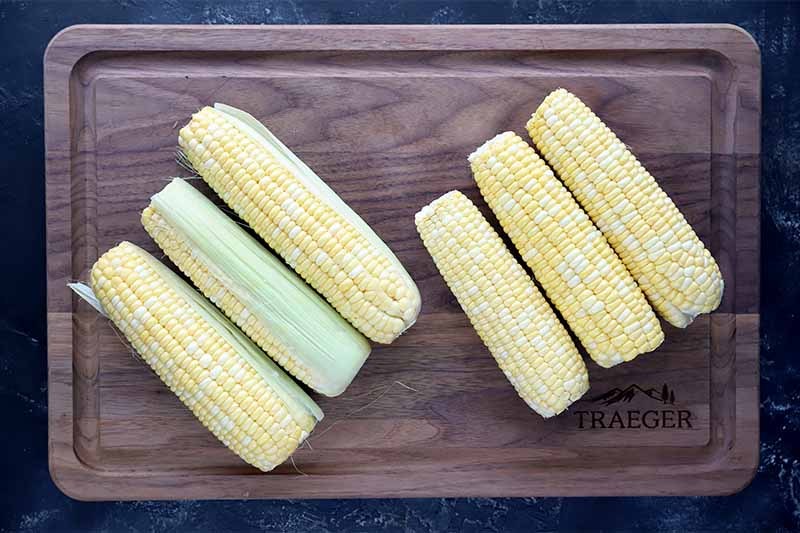 Horizontal image of six ears of corn on a wooden cutting board.