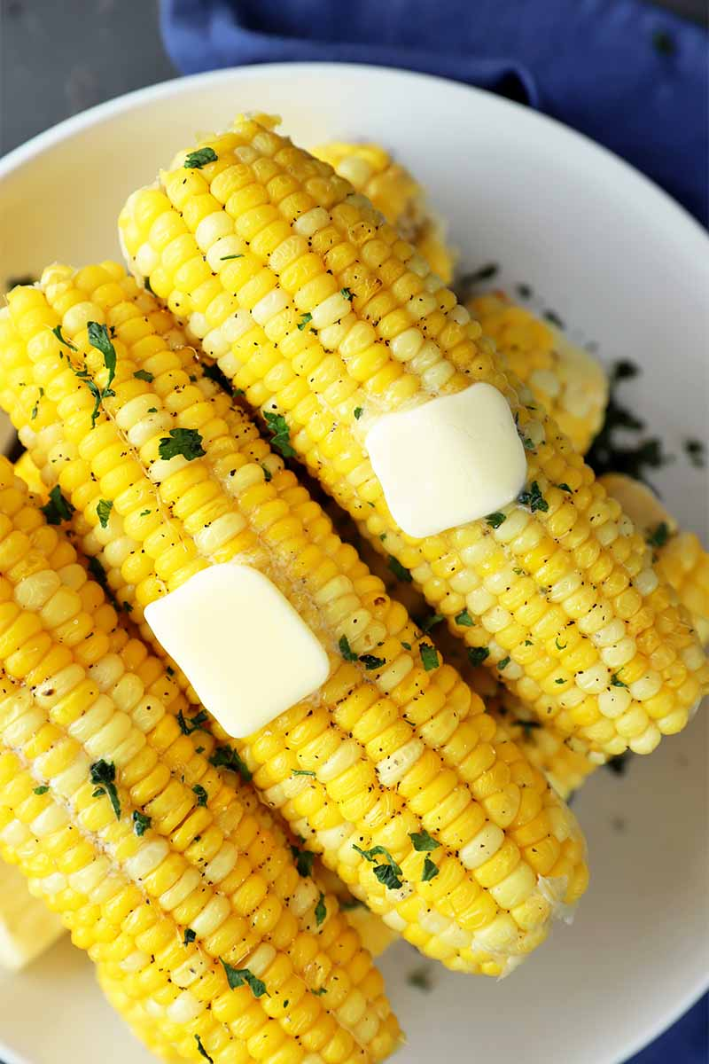 Vertical top-down image of a stack of ears of corn topped with chopped herbs and butter on a white plate.